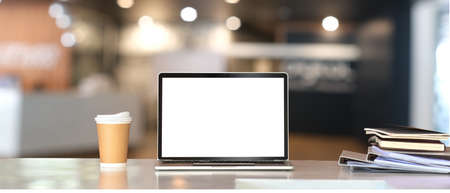 Empty screen laptop, a coffee paper cup with a stack of notebook on a table.