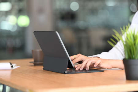 Young business woman using digital tablet on wooden table. 免版税图像