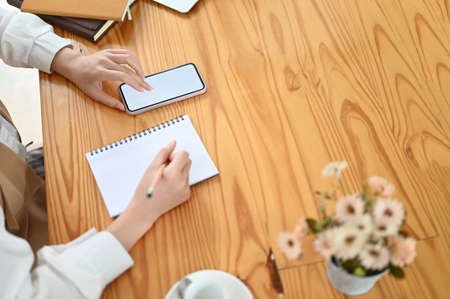 Young business woman using smart phone with white screen while taking notes in notebook on wooden table.