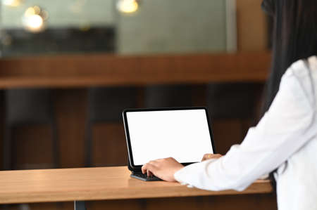 business woman typing on a laptop with empty white screen.