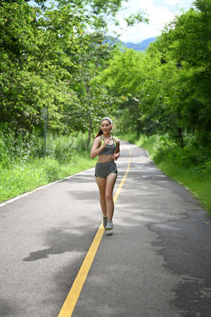 Sport girl jogging along a country road in spring sunshine during her daily workout.