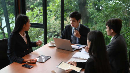 Businessman explaining new business ideas to peers in meeting room.