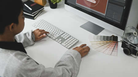 Young graphic designer woman using digital graphic tablet while working in modern office. Stock Photo