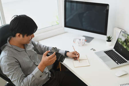 Cropped shot of a young designer sitting at graphic studio in front of computer while working online.