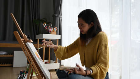 Side  view of cheerful young woman painter is drawing and sitting on the floor in front of a canvas. 版權商用圖片
