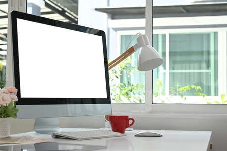 Close up view of young designer is sitting at workplace and using mobile phone with blank screen.