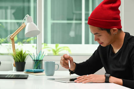 Graphic designer in red wool hat working on digital tablet and looking at camera while sitting at his workplace. Banco de Imagens