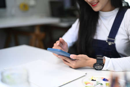Cheerful young female Graphic designer holding stylus pen drawing on tablet. Banco de Imagens