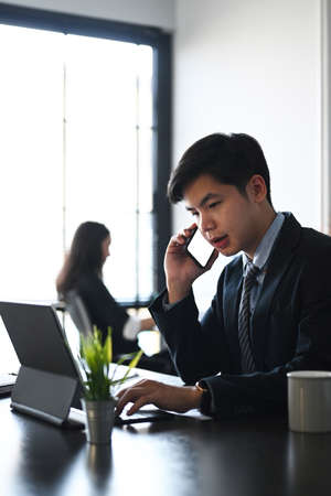 Two young businesspeople in black suit scrolling through online information while getting ready with presentation.