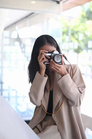 Beautiful female photographer checking photos in camera while sitting at her studio.