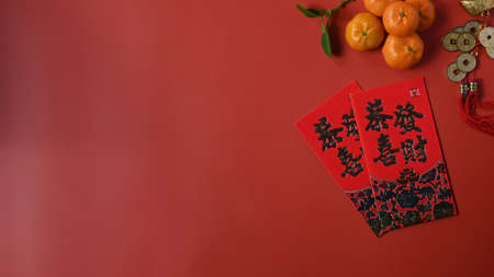 Top view accessories Chinese new year festival decorations with orange, red packet and copy space on red background.
