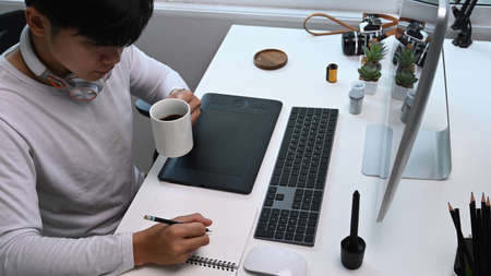 High angle view of young man photographer drinking coffee and making note at his workstation.