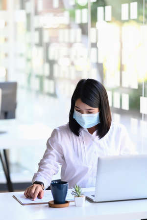 Female entrepreneur wearing face mask while working on a computer and writing notes in modern office.