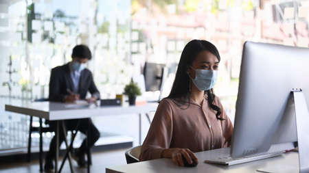 Businesspeople or office worker are wearing medical mask and working in office room.