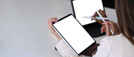 Close up view of female designer holding stylus pen pointing on screen of tablet computer. 免版税图像