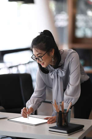 Portrait of cheerful woman in eye glasses standing at her workspace and using digital tablet. 免版税图像