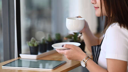 Asian female owner coffee shop holding cup of coffee and tasting brewed coffee.