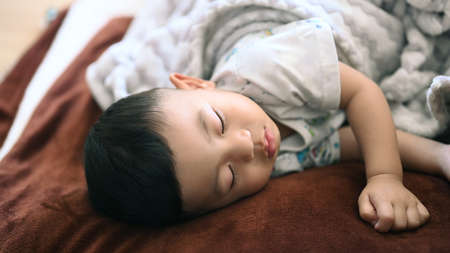 Close up view of baby boy sleeping on bed at home.
