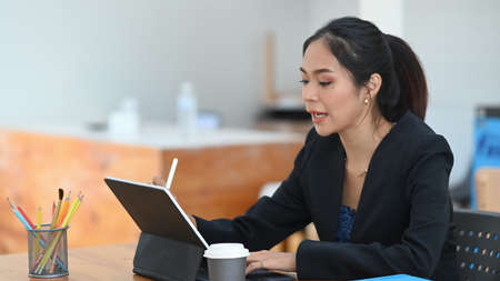 Young businesswoman using digitizer pen writing on screen of digital tablet while sitting a her workplace. Banco de Imagens