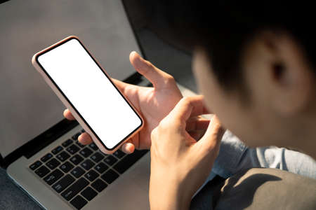Overhead shot of businessman holding horizontal smart phone with blank screen at his workplace.