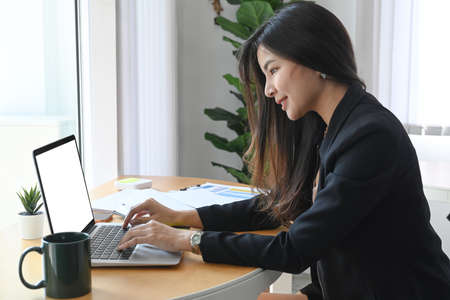attractive businesswoman sitting with her colleague in office and making business call.