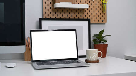 Close up view mock up computer laptop with blank screen on white desk at home office.