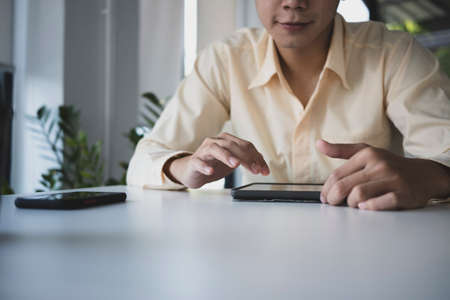 Cropped shot of businessman reading online information on digital tablet in office. Stock Photo