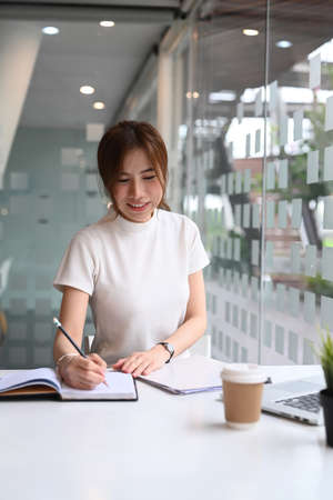 Portrait of successful businesswoman holding pen and thinking about her work at modern office. Stock Photo