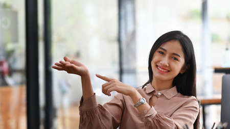 Young businesswoman smiling and presenting something. Stock Photo