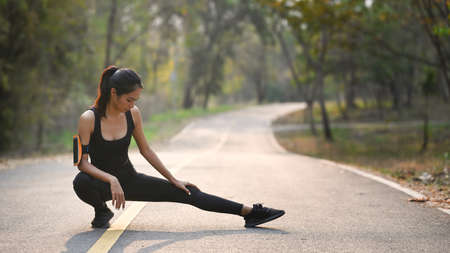 Young asian woman stretching her legs before exercises outdoors.