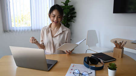 Cheerful businesswoman having video call with colleagues on laptop computer in office.