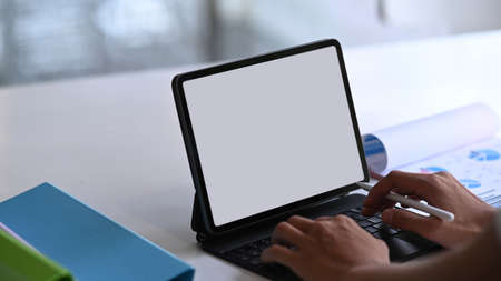 Mock up computer tablet with blank screen and a bowl of popcorn on white table. Stock Photo