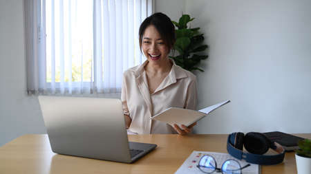 Cheerful businesswoman having video call via laptop in the office.