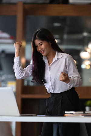 Successful businesswoman looking at laptop computer and raising her arm up to celebrating her success.