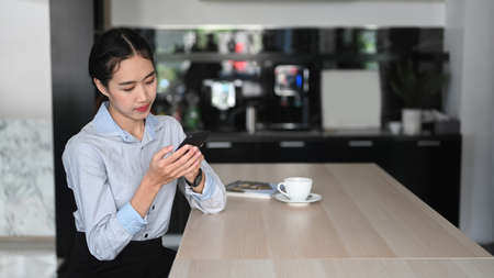 Young asian woman employee using mobile phone during coffee break in office.