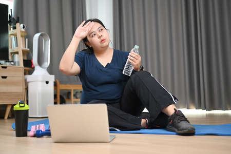Tired young obese woman sitting and resting after doing fitness exercises at home.
