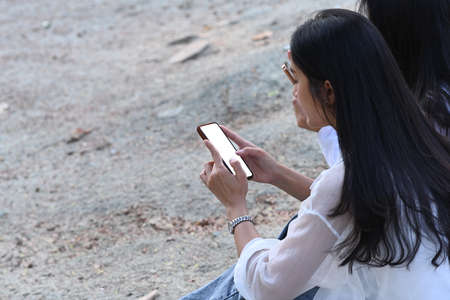 Two young asian woman sitting at outdoor and using mobile phone. Stock fotó