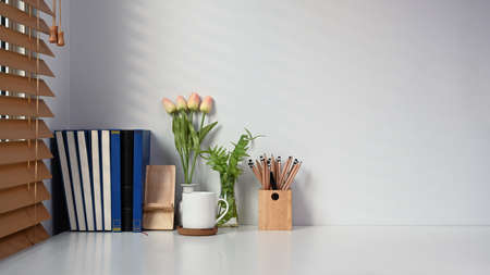 Contemporary workspace with book, coffee cup, pencil holder and flowers on white table. Stock fotó