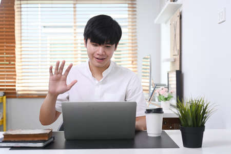 Young asian man sitting in modern office and video conference with his colleagues on laptop computer.