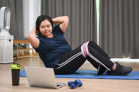 Overweight woman exercising with fitness rubber band at home.  Weight loss and healthy lifestyle.