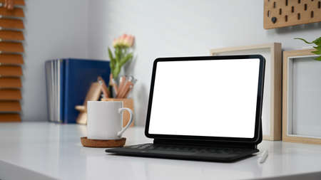 Mock up computer tablet with blank screen, coffee cup and supplies on white desk.