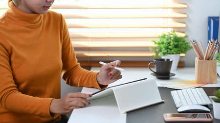 Cropped shot of stylish woman working with digital tablet while siting in modern office. Stock fotó