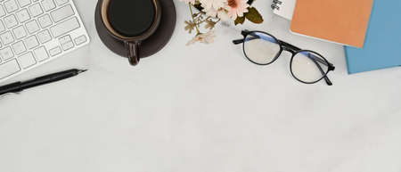 Top view of white office desk with coffee cup, glasses, notebook and plant.