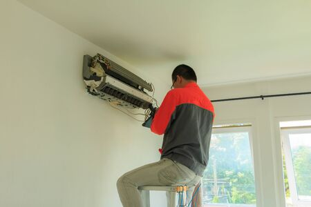 a man is repairing air-conditioning on the wall in the white room Stock Photo