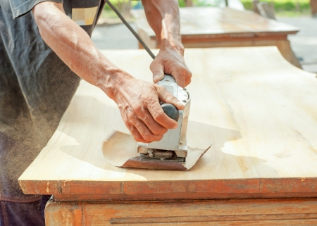 Hand of worker sanding the old wood table
