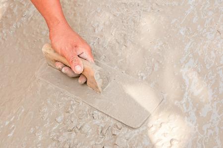Asian plasterer hand plastering a floor photo