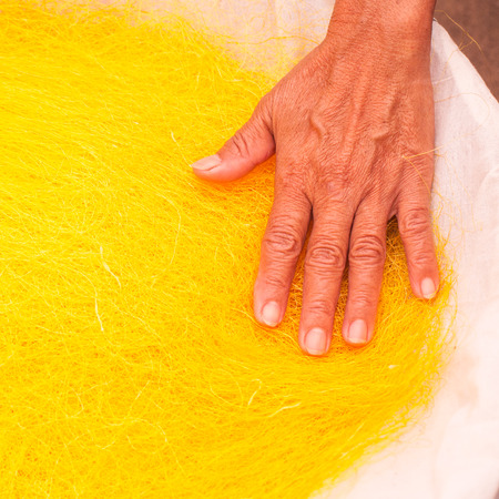 Old women hand with  on yellow silks photo