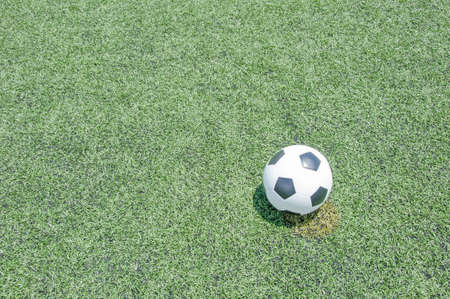 Close up soccer ball on green grass or artificial turf at noon photo