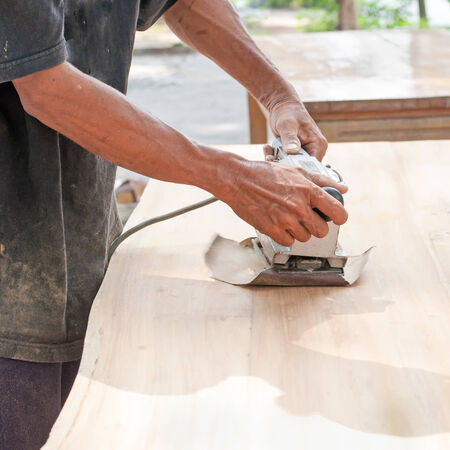 Hand of worker sanding the old wood table. photo