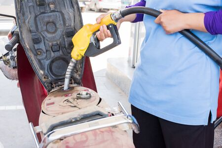 hand fuel nozzle in pouring to motorcycle at gas station